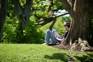 Male-College-Student-Reading-Outside-By-A-Tree-In-The-Spring